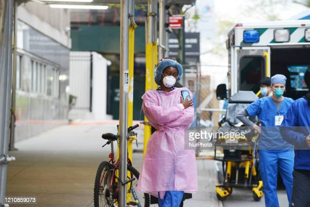 Tired nurses stand outside the entrance to Mt. Sinai Morningside Hospital in New York City, Thursday, 23 April, 2020.