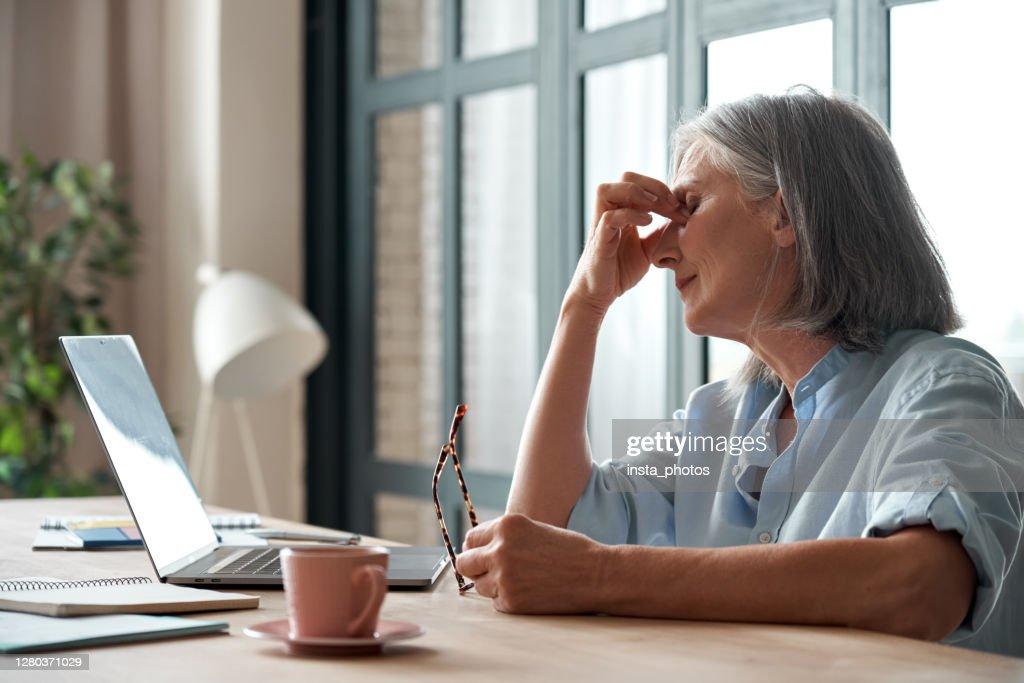 De vermoeide oude hogere bedrijfsvrouw die glazen neemt lijdt aan vermoeide ogen, spanning, hoofdpijn, moeheid na computergebruikswerk in bureau. Uitgeputte zieke rijpe dame voelt oogspanningsprobleem op de werkplek : Stockfoto