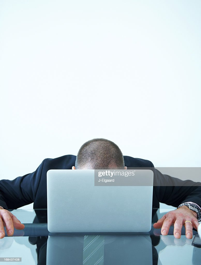 Tired Or Stressed Out Businessman Behind His Laptop At Desk