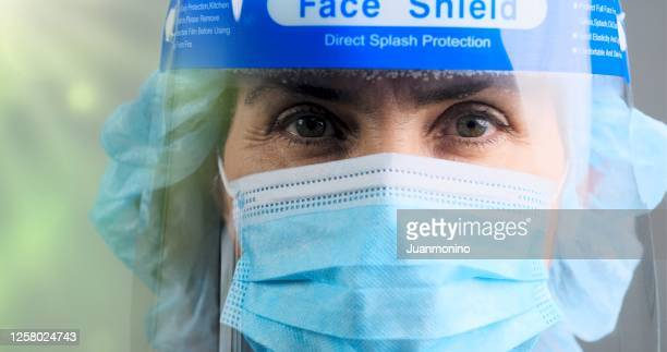 tired, overworked, exhausted health care worker wearing a mask and a face shield posing looking at the camera - face shield stock pictures, royalty-free photos & images