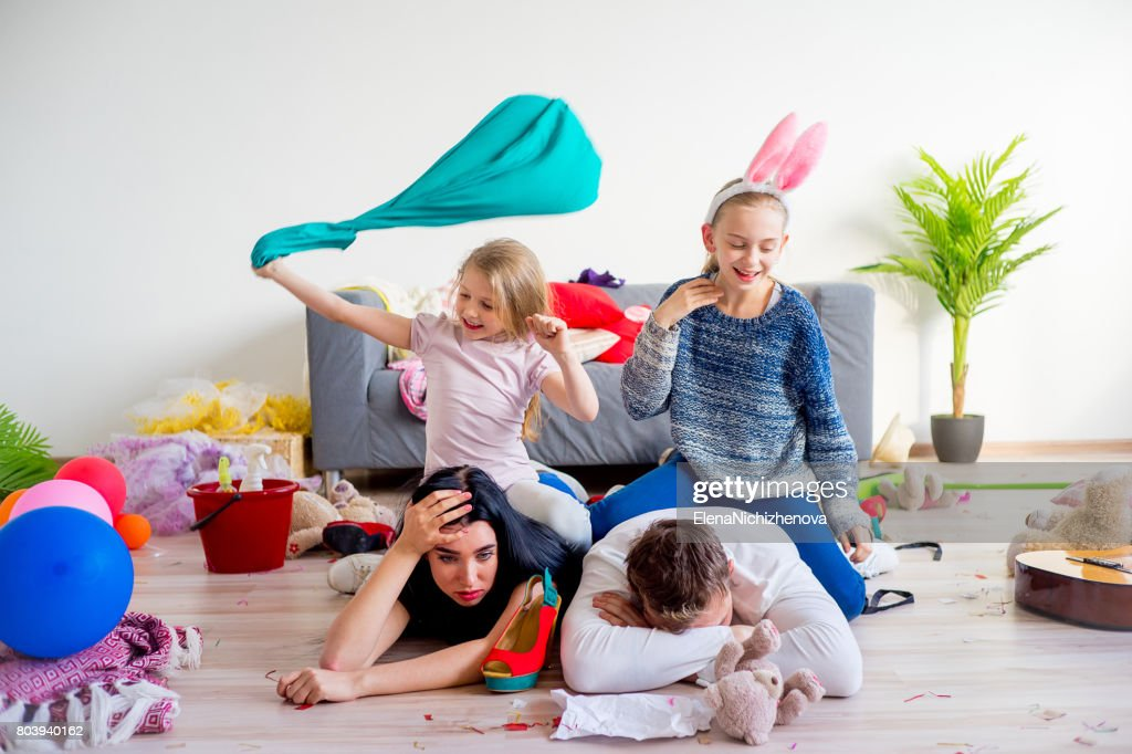 Tired parents and romping kids : Stock Photo