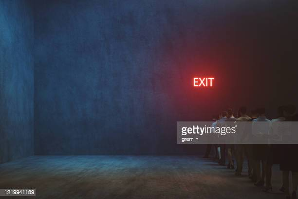 tired people waiting in front of exit sign - exit sign stock pictures, royalty-free photos & images