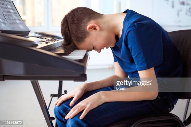 tired pre-adolescent boy in piano class - keyboard player stock pictures, royalty-free photos & images