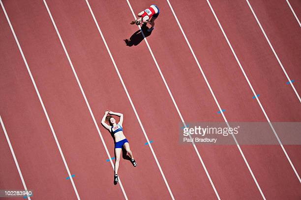 tired runner laying on track - defeat stock photos and pictures
