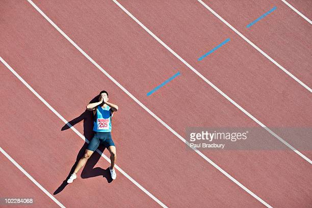 tired runner laying on track - nederlaag stockfoto's en -beelden