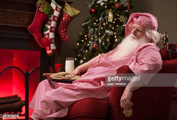 Tired Santa Asleep with Milk and Cookies by Fireplace