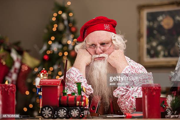 tired santa in workshop - santas workshop stock photos and pictures