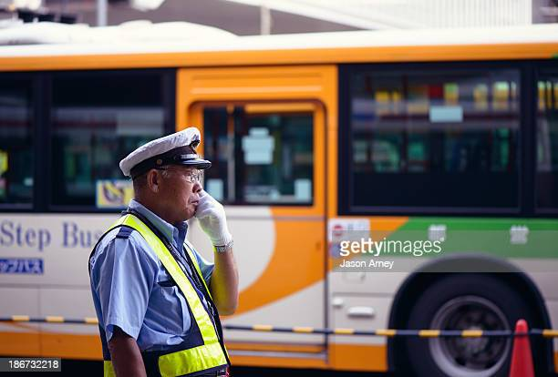 Tired security attendant adjusts his glasses while directing the busy terminal at Shibuya train station in Tokyo Japan.