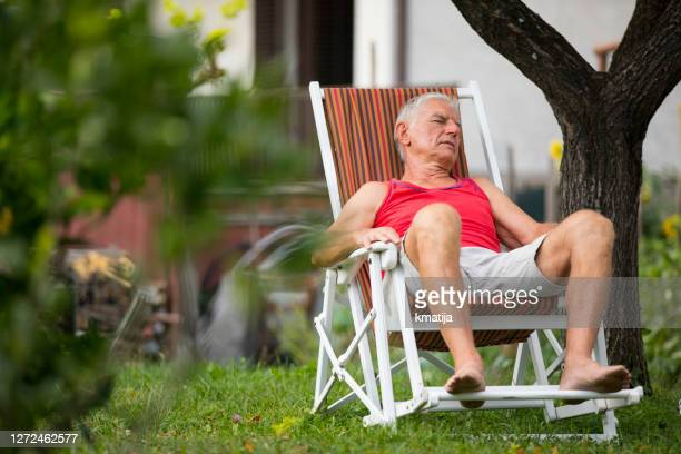 tired senior adult man napping on lounge chair in backyard - chairperson stock pictures, royalty-free photos & images