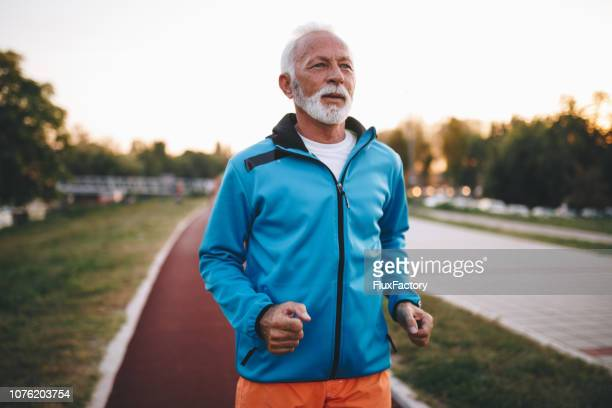 tired senior man running on a track - good posture stock pictures, royalty-free photos & images