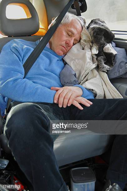 Tired Senior man sleeping in car with safety belt