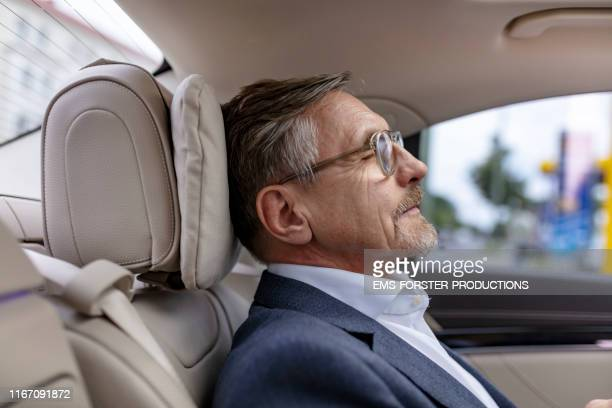 tired senior manager is relaxing in his limousine while getting chauffeured - limousine stock pictures, royalty-free photos & images