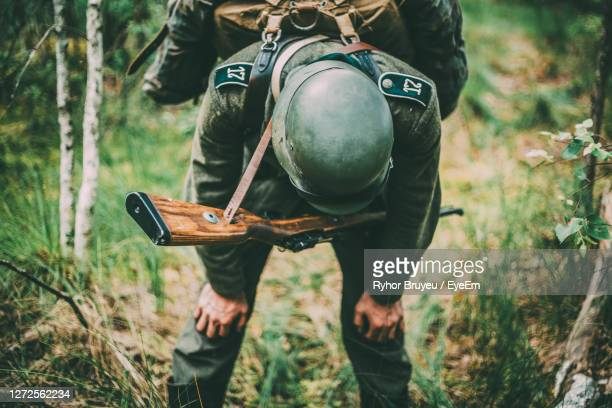 tired soldier with rifle standing in forest - german military stock pictures, royalty-free photos & images