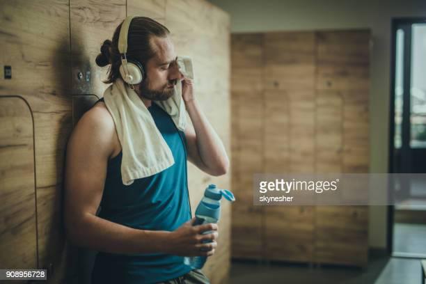 Müde Sportler hören Musik während der Schweiß aus dem Gesicht wischte, bei einer Pause im Umkleideraum.