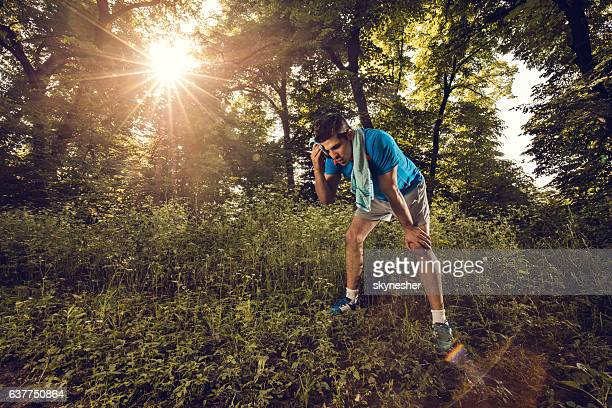 Tired sportsman wiping sweat from his forehead in nature.