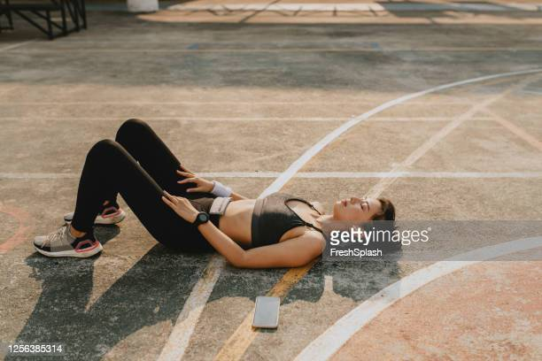 tired sportswoman lying on the court to rest during an outdoor workout - lying down stock pictures, royalty-free photos & images