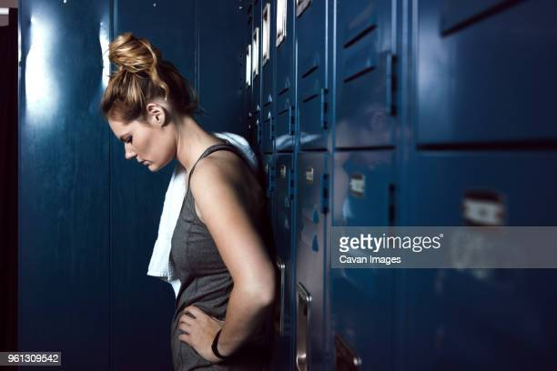 tired sportswoman standing against lockers in gym - 女性選手 ストックフォトと画像
