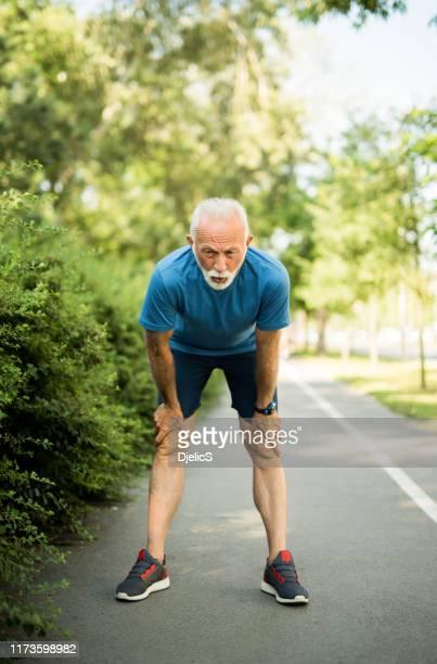 müde sportlicher senior mann ruht sich vom laufen. - raucher lunge stock-fotos und bilder
