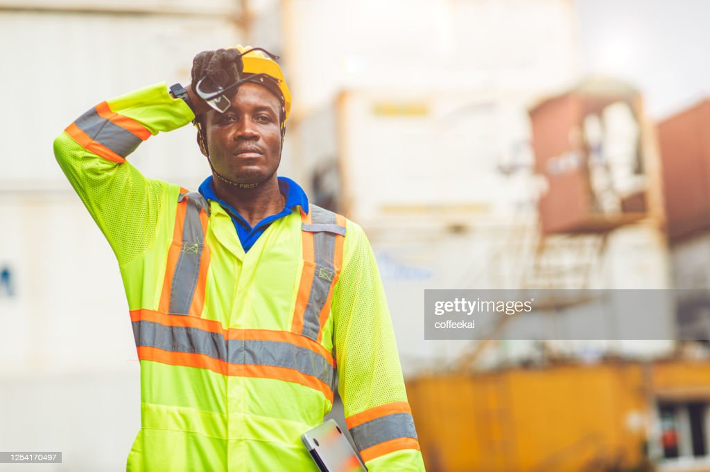 Tired stress worker sweat from hot weather in summer working in port goods cargo shipping logistic ground,  Black African race people. : Stock Photo