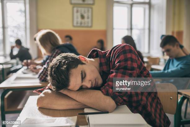 Tired student taking a nap during a lecture in the classroom.