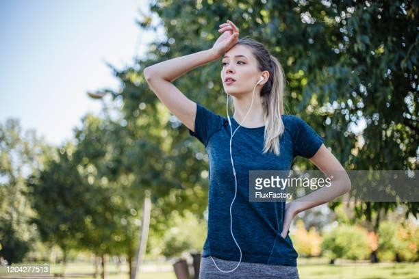 長い朝の実行後にリラックス疲れた汗をかく女性 - extra long ストックフォトと画像