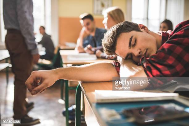 tired teenage boy napping at school during the class. - tired stock pictures, royalty-free photos & images