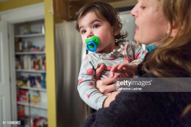 tired toddler and mother. todder is looking away with pacifier in mouth and mom is trying to soothe. - pacifier stock pictures, royalty-free photos & images