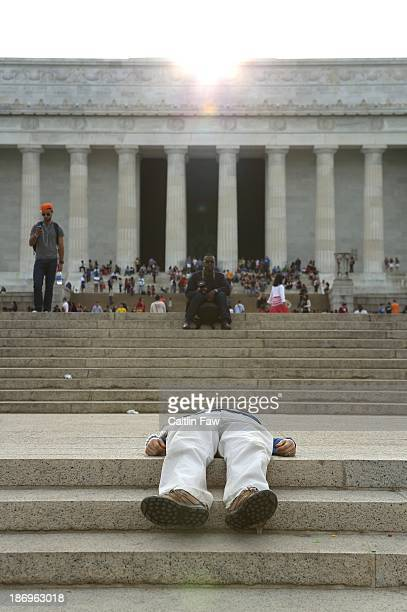 Tired tourist lies down on the steps in front of the Lincoln Memorial in Washington, DC on a sunny day in the city.