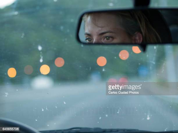 Tired woman driving at dusk on a highway