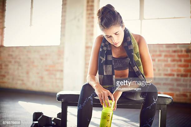Tired woman holding water bottle in gym