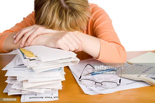 Tired woman in a heap of undone accounting report