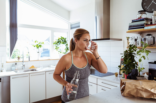 Tired woman in sports clothing drinking water while standing at kitchen - gettyimageskorea