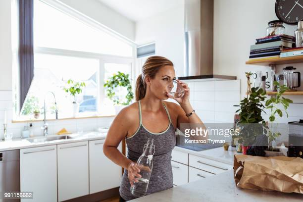 tired woman in sports clothing drinking water while standing at kitchen - drinking water stock pictures, royalty-free photos & images