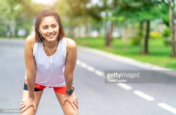 tired woman runner taking a rest after running hard in the park. sweating fitness woman tired exausted of running in sun heat dehydrated with sweat dripping from face. athlete jogger jogging outside in city. - southeast asia stock pictures, royalty-free photos & images
