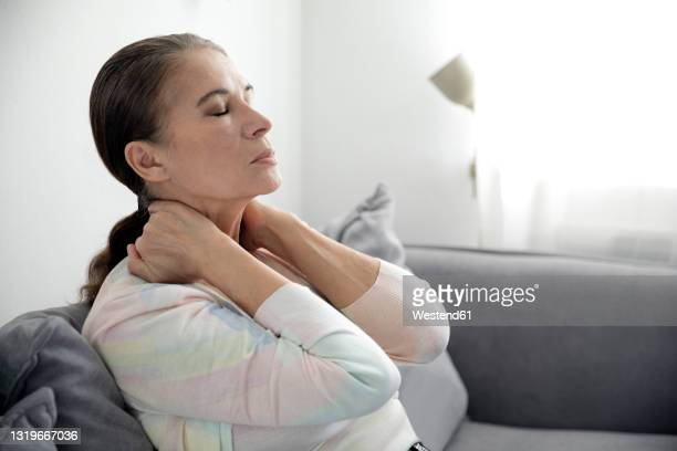 tired woman siting with eyes closed on sofa - tired stock pictures, royalty-free photos & images