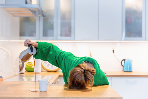 Tired woman sleeping on the table in the kitchen at breakfast. Trying to drink morning coffee 1059134652