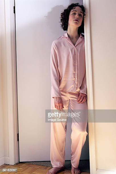 Tired woman standing in doorway