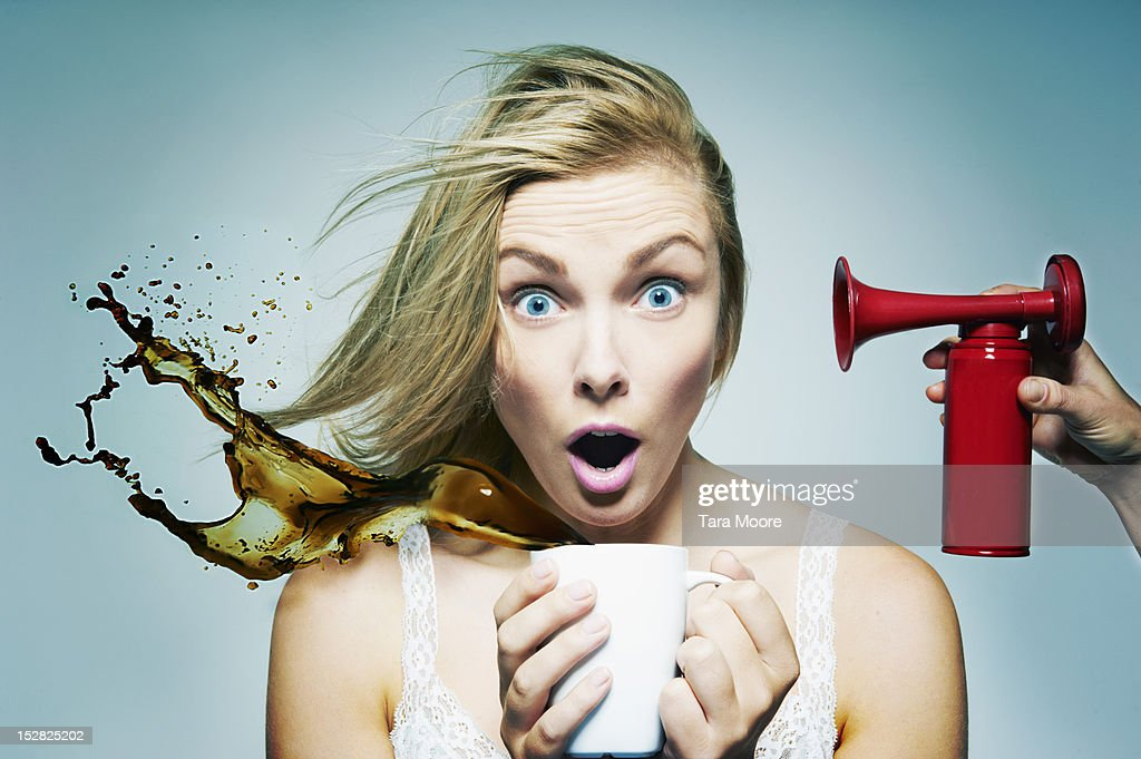 tired woman staying awake with coffee and air horn : Stock Photo