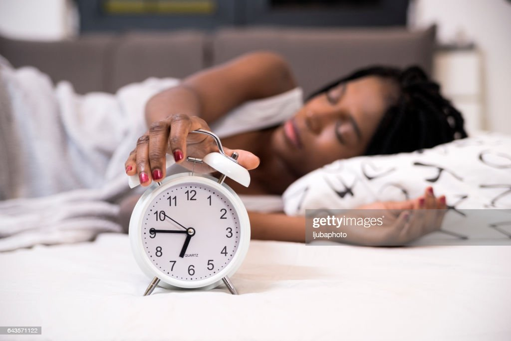 Tired Woman Switching Off Her Alarm Clock In Her Bedroom : Stock Photo