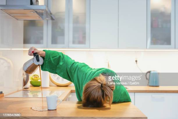 tired woman trying to drink morning coffee and sleeping on the table - moe stockfoto's en -beelden