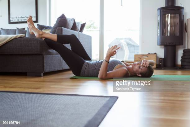 tired woman using mobile phone while lying on exercise mat in living room - sports training stock pictures, royalty-free photos & images