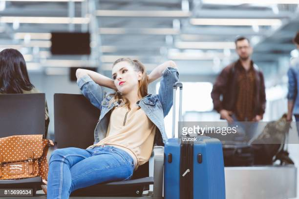tired woman waiting for delayed flight in airport terminal - izusek stock pictures, royalty-free photos & images