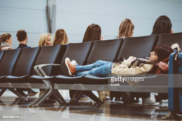 Tired woman waiting for delayed flight in airport terminal