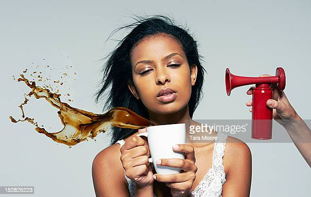 tired woman with coffee and air horn