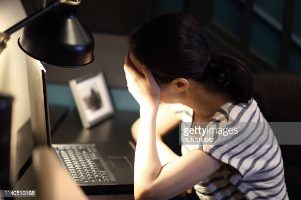 tired woman with head in hand on desk at home - フリーランス ストックフォトと画像