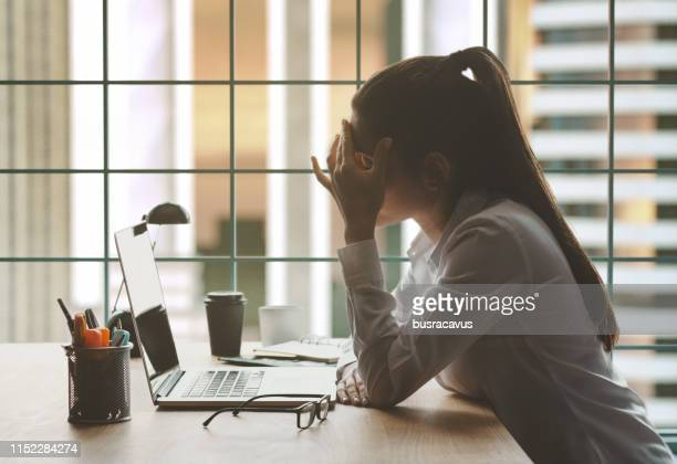tired woman working on laptop in office - concentrazione foto e immagini stock