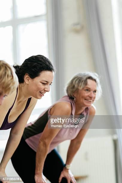 Fatigué femme avec les mains sur les genoux souriant dans la salle de sport