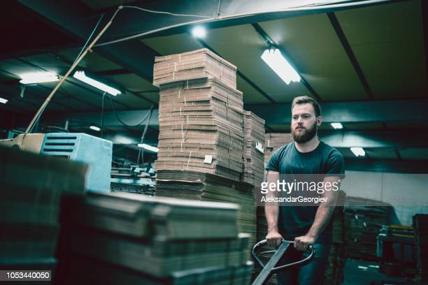 Tired Worker Pushing Cardboard Carton Planks On Transportation Cart on Night Shift