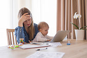 Tired working mom with child in her lap feeling exhausted