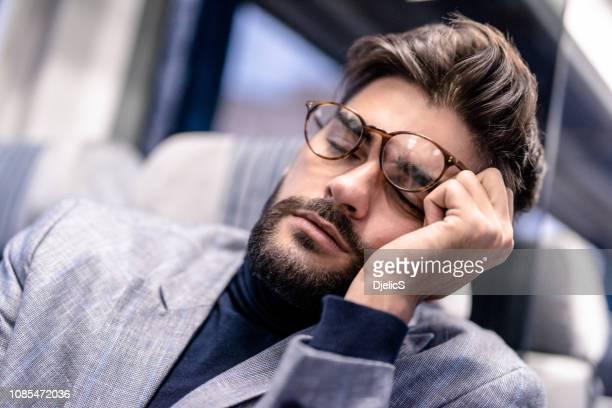 müde junger geschäftsmann schlafen während der fahrt mit dem zug. - bahnreisender stock-fotos und bilder